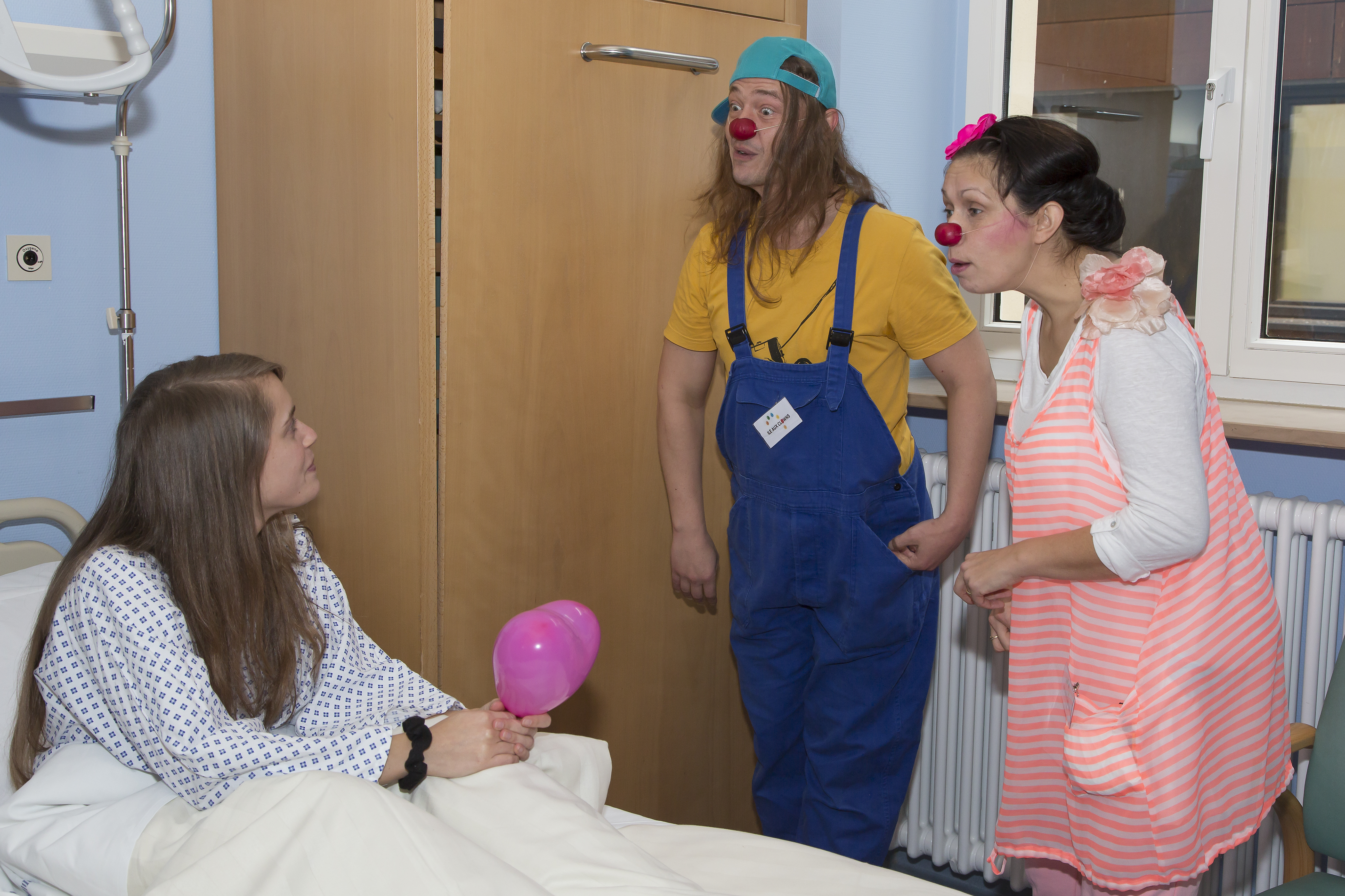 Clowns making a young girl laugh